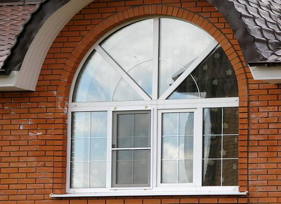 Арочное пластиковое окно в кирпичном доме